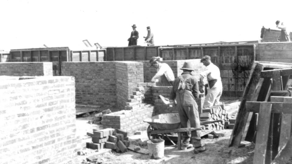 Une photo en noir et blanc de travailleurs lors de la construction de la cathédrale de Gravelbourg.