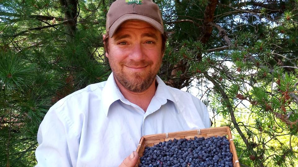Aaron Shantz avec un casseau de bleuets.