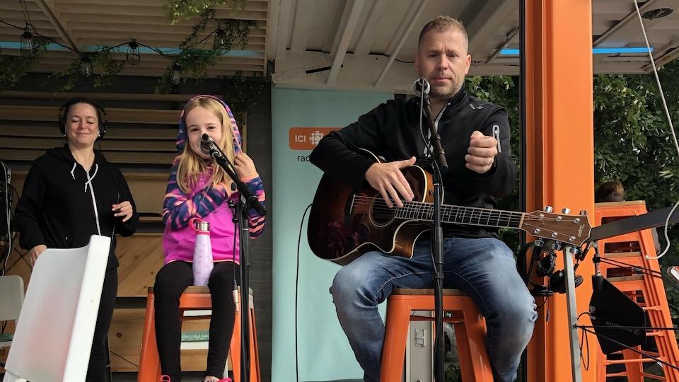 Une jeune fille et son père sont assis sur des tabourets sur une scène. Ils sont chacun derrière un microphone et l'homme tient une guitare.