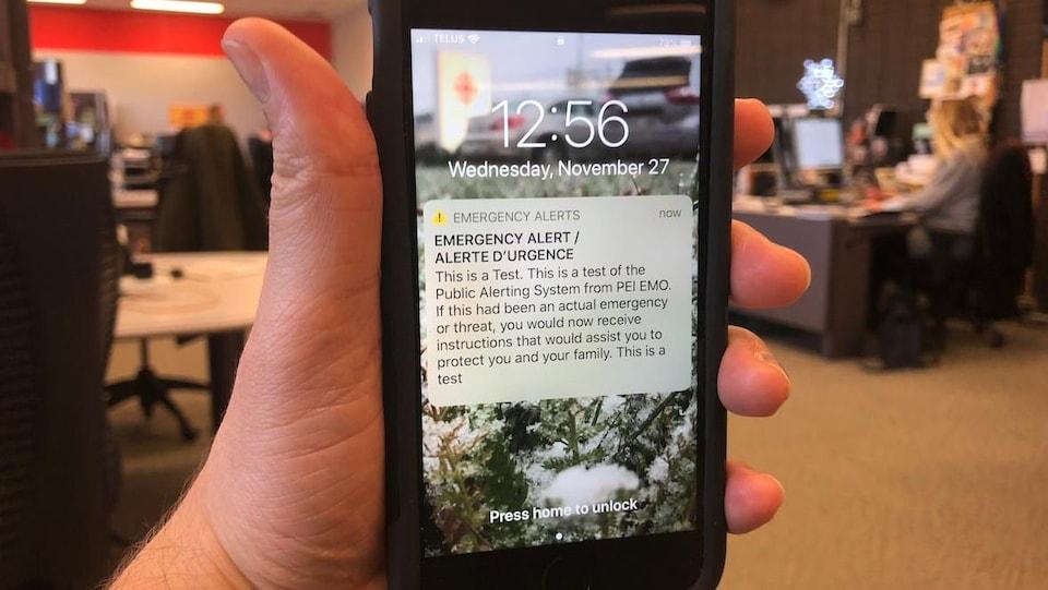 Une personne qui tient un cellulaire sur la main. Un message d'alerte en anglais apparaît à l'écran.