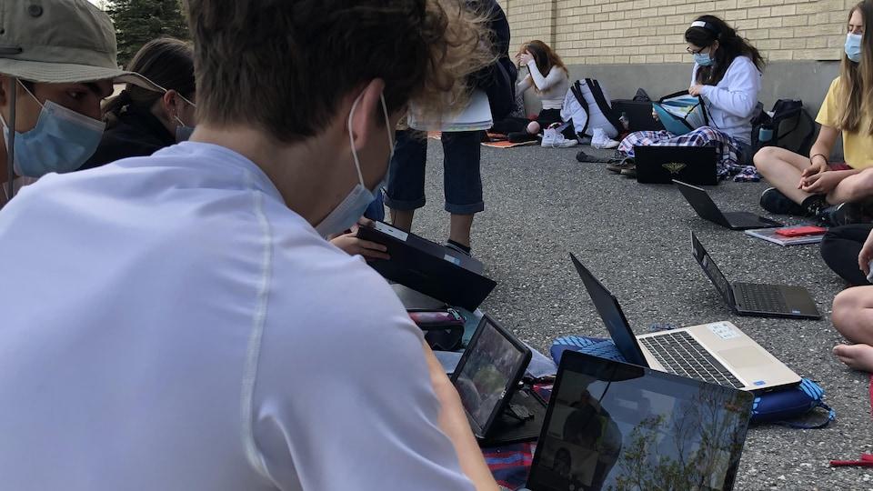 Des élèves penchés sur des tablettes et des ordinateurs portables.