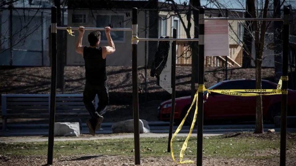 Un homme fait des tractions à l'aide d'une barre métallique dans un parc
