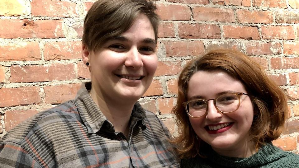 Deux femmes photographiées devant un mur de briques. Elles sourient.