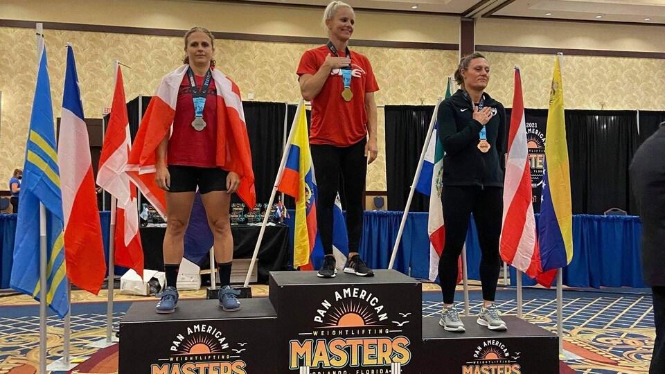 Trois athlètes féminines d'haltérophilie sur un podium.