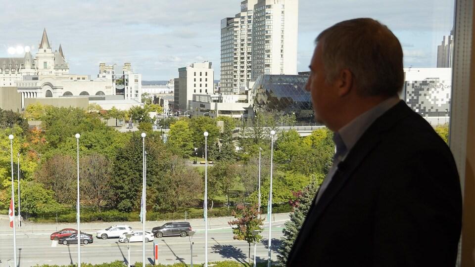 Anthony Di Monte qui regarde un paysage de la ville d'Ottawa par une fenêtre.