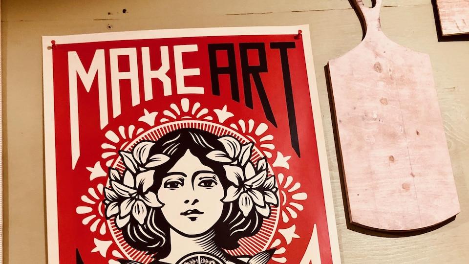 Une affiche rouge sur laquelle on peut lire : « Make art not war »