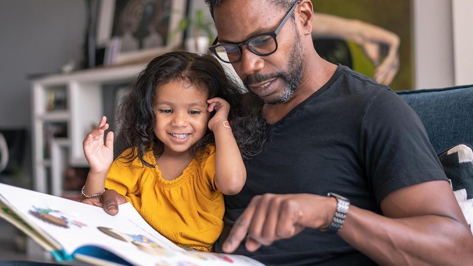 Une fillette et son père en train de livre un livre.