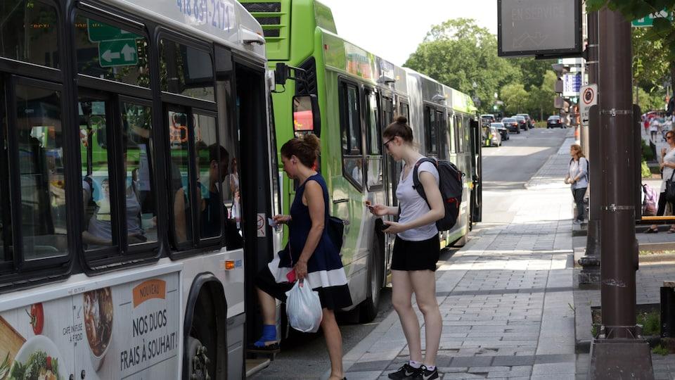 Deux femmes montent à bord d'un autobus du RTC en été.