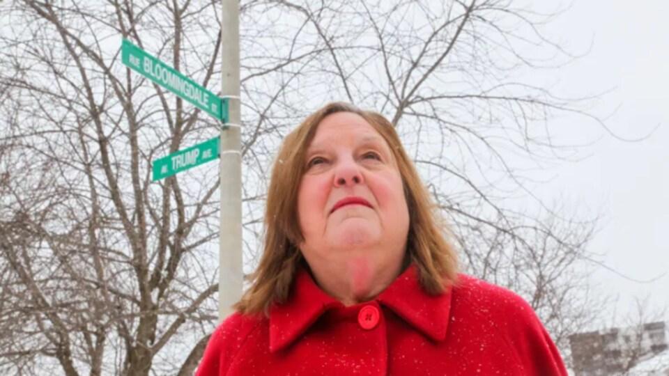 Bonnie Bowering devant la caméra au coin de l'avenue Trump et de la rue Bloomingdale.
