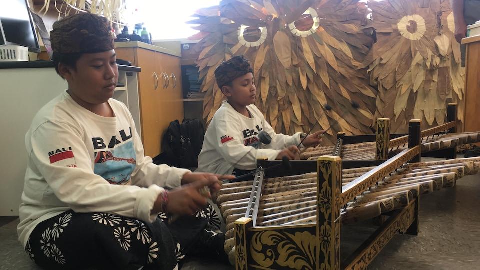 Les deux enfants sont installés devant des xylophones indonésiens et des cerfs-volants en forme de hiboux.