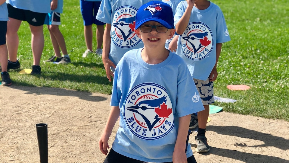Des jeunes arborant des chandails des Blue Jays de Toronto s'apprêtent à frapper la balle.