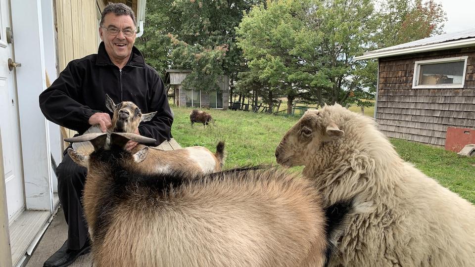 Benoit Thibodeau, alias Ben Lalen, accompagné de chèvres et d'un mouton de sa fermette, située derrière sa boutique.