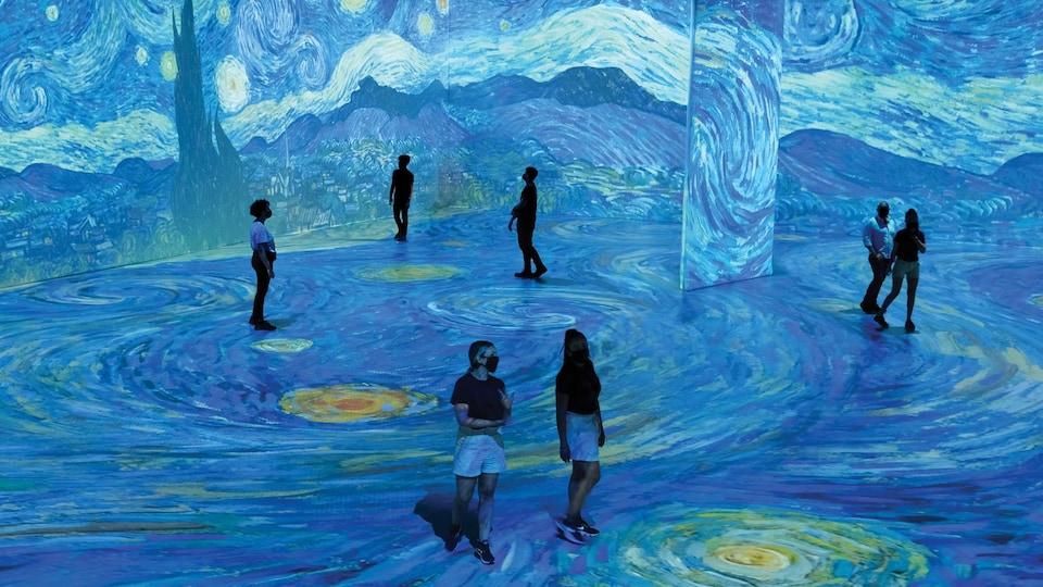Des personnes dans une pièce ou La nuit étoilée de Van Gogh est projetée sur le plancher et les murs.