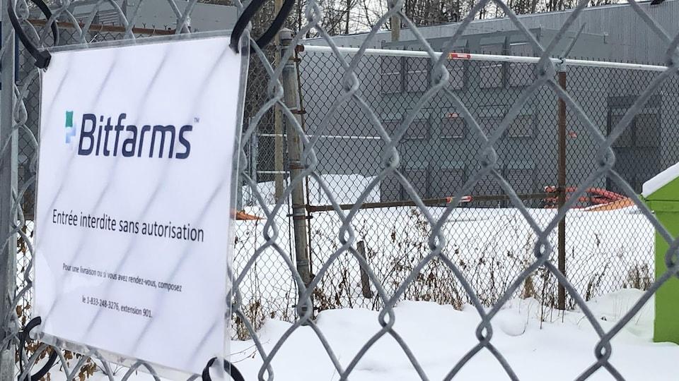 Les murs de l'usine Bitfarms. Une affiche indique qu'il est interdit d'y entrer sans autorisation.