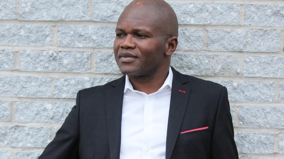 Blaise Ndala appuyé sur un mur de brique.