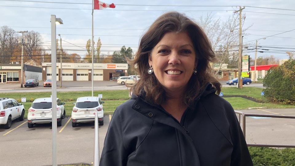 Une femme souriante portant un manteau noir, devant l'édifice de Radio-Canada, à Charlottetown. Quelques voitures stationnées et le drapeau du Canada se trouvent au fond.