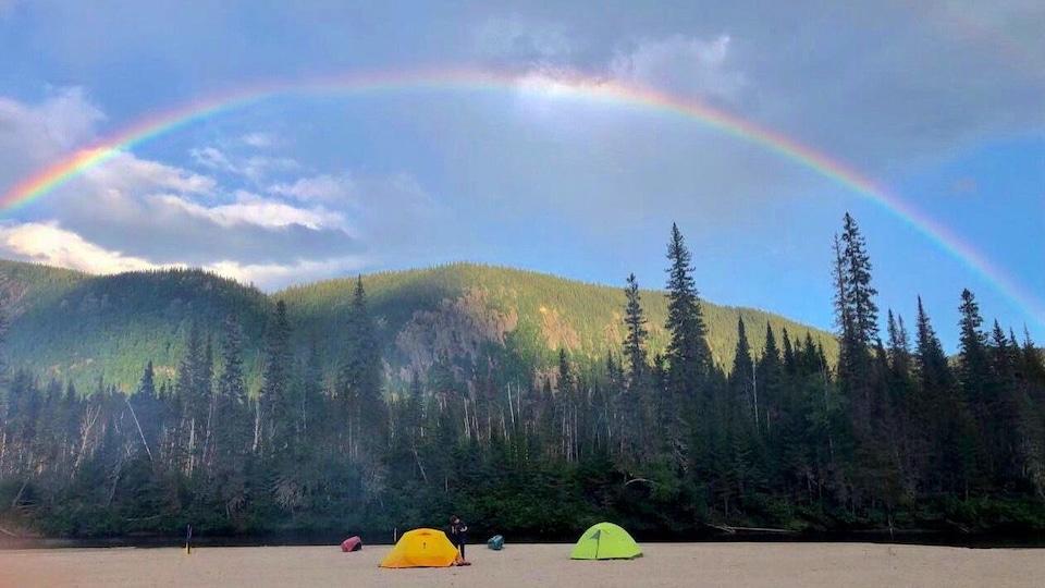 Des tentes se trouvent sur une plage surmontée d'un arc-en-ciel.
