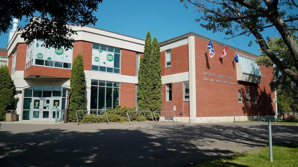 Devant du bâtiment, un jour ensoleillé d'été avec des zones d'ombres. On peut lire l'inscription Faculté Saint-Jean sur le côté.