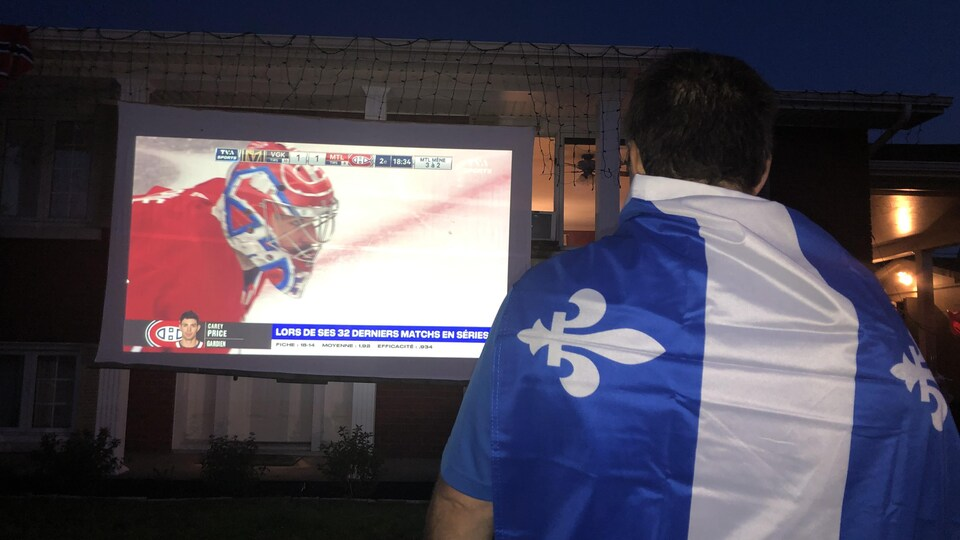 Un homme portant un drapeau du Québec regarde un match du Canadien.