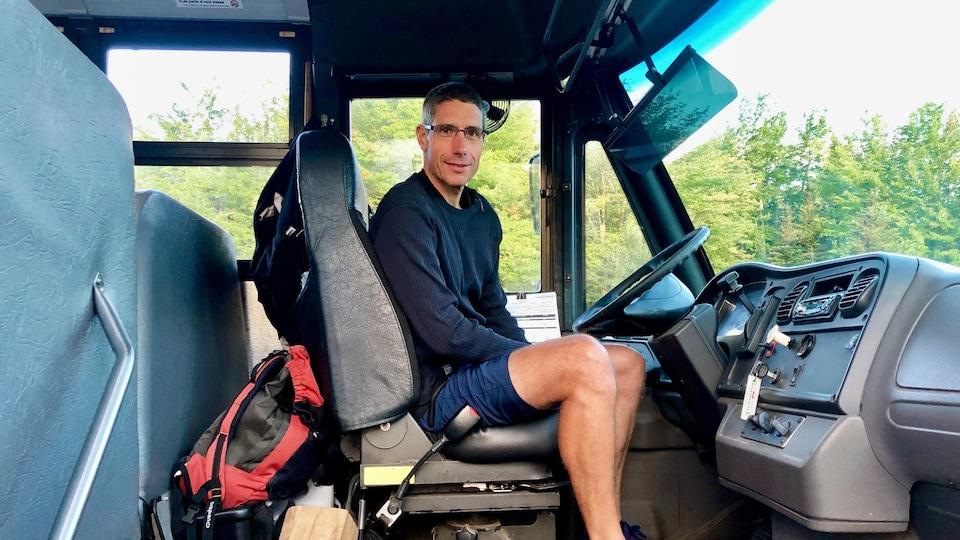Olivier Valton assit au volant de son autobus scolaire.
