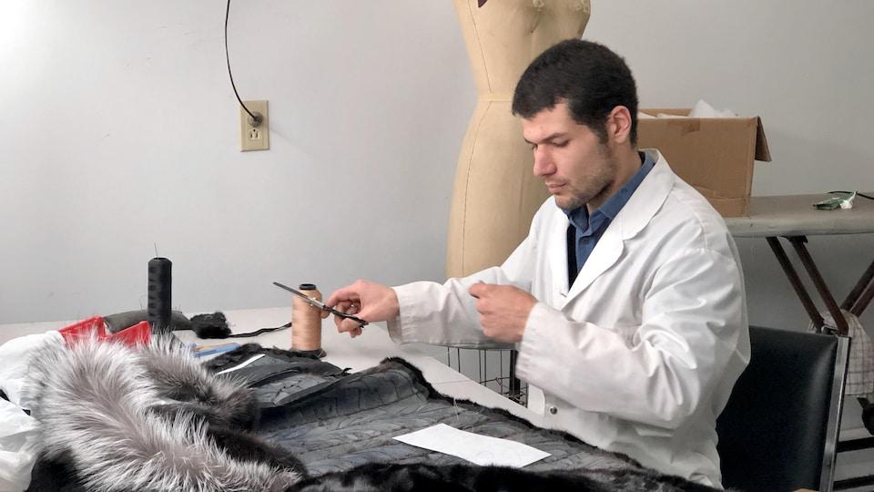 Le tailleur travaille sur un manteau de fourrures.