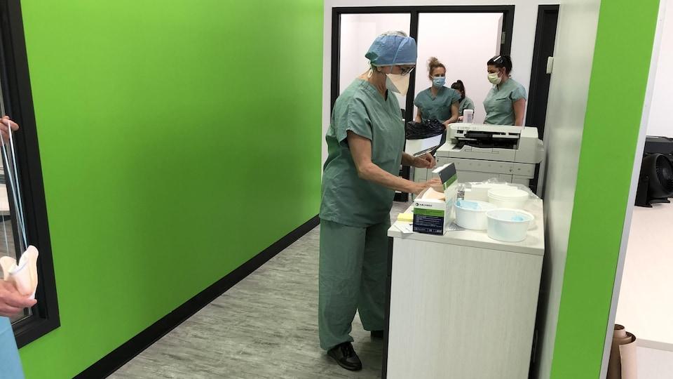 Trois professionnels de la santé portant le masque de procédure et un uniforme médical oeuvrent à la clinique de dépisage de Plessisville, dont les mûrs sont d'un vert éclatant. L'un des employés travaille à une table où sont posés une boîte de masques ainsi que plusieurs récipients blancs dans lesquels se trouvent des instruments de travail.