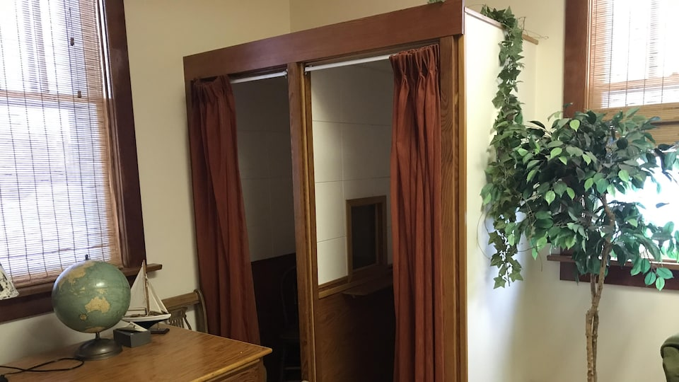 Un confessionnal dans le coin d'une salle. Il y a aussi une grande plante et un globe terrestre sur un bureau.