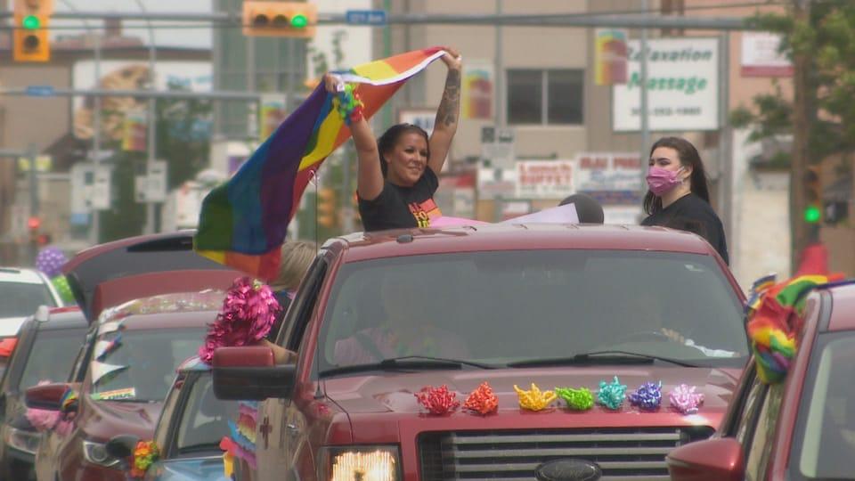 Une femme tenant un drapeau LGBTQ+ debout dans un pickup décoré. Un autre femme à côté avec un masque sur le visage. File de voitures décorées aux couleurs de l'arc en ciel.