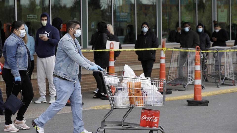 Un homme pousse un caddie de supermarché devant une file d'attente de clients. Tous sont masqués.