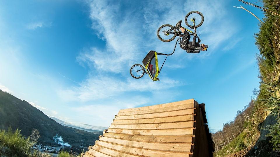 Image tirée du film Danny Daycare, du cycliste et photographe Danny MacAskill. On y voit un cycliste dans les airs, en train de faire un tour sur lui-même, avec un chariot pour enfant attaché à son vélo.