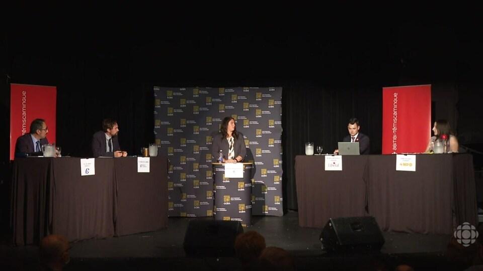 Sur une scène noire, quatre candidats et une animatrice se préparent à débattre.