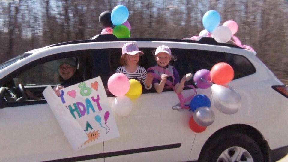 Deux petites filles sortent leur tête d'une voiture décorée avec plein de ballons d'anniversaire.