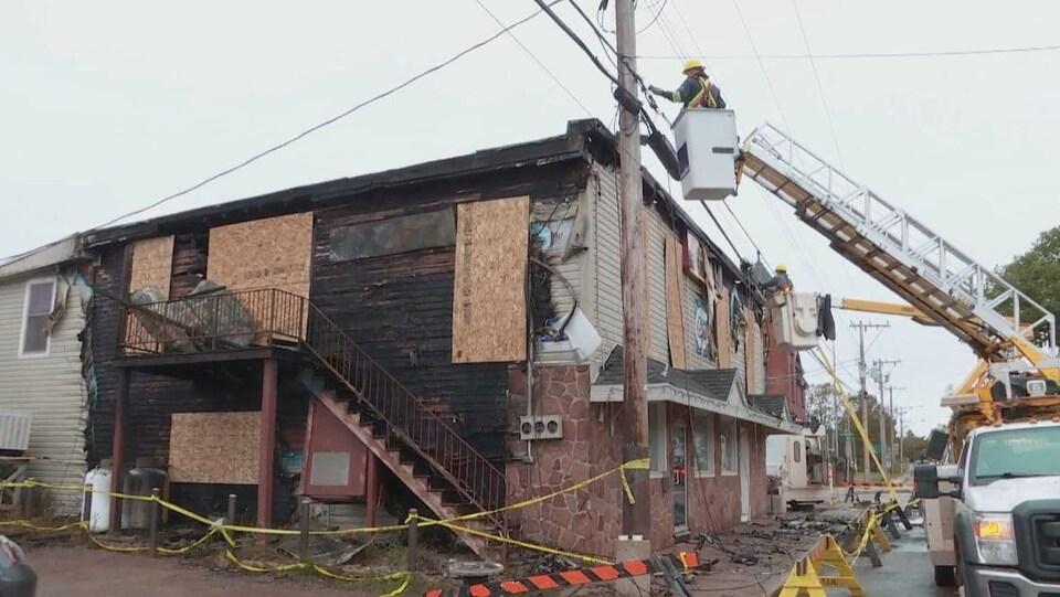 Un bâtiment ravagé par le feu et un employé de la Ville qui fait des travaux dans le réseau électrique