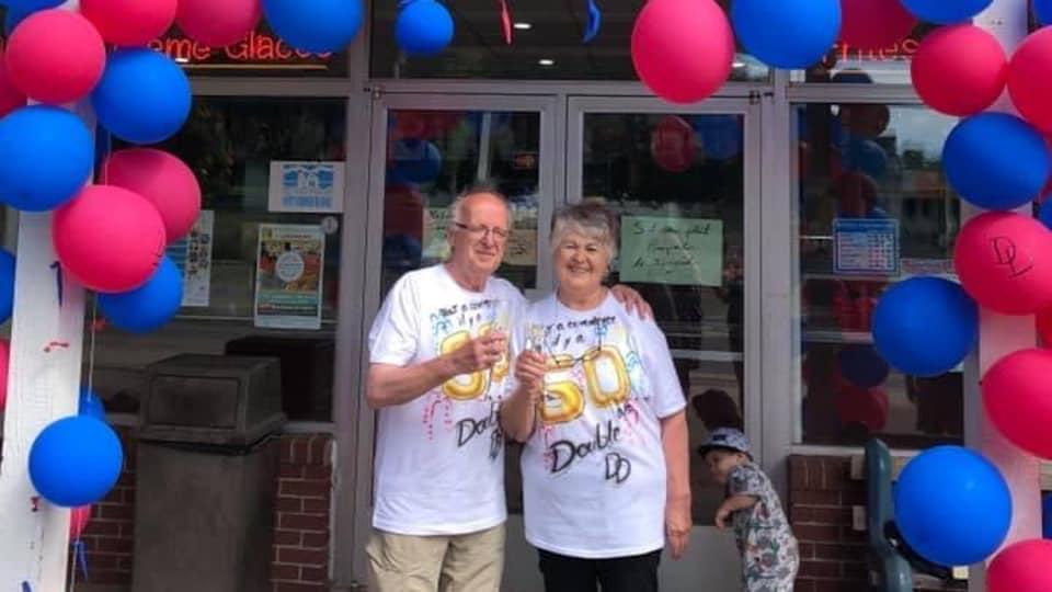 Donat et Doris Cormier sont debout devant leur restaurant lors d'une fête. Il y a plusieurs ballons et ils ont une boisson à la main.