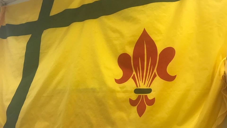 Un drapeau fransaskois, une croix verte et une fleur de lys rouge sur fond jaune.