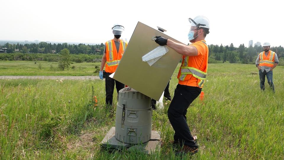 Un homme soulève une boîte métallique révélant un grand contenant en plastique.
