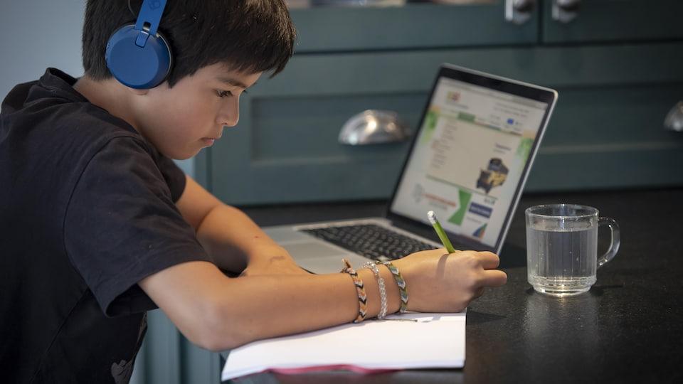 Un enfant suit une classe en ligne, alors que les écoles sont fermées.