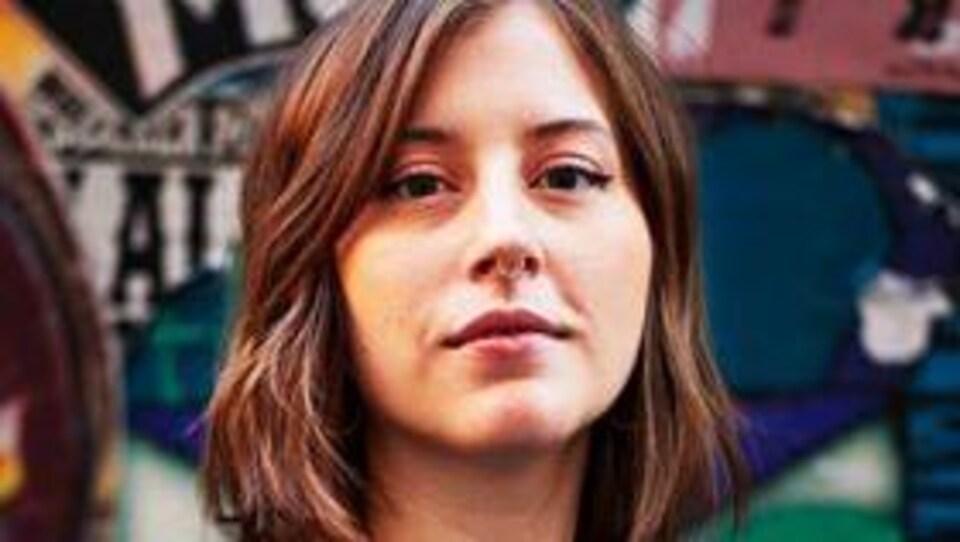 La journaliste Elisabeth Massicolli pose devant un mur d'art de rue.