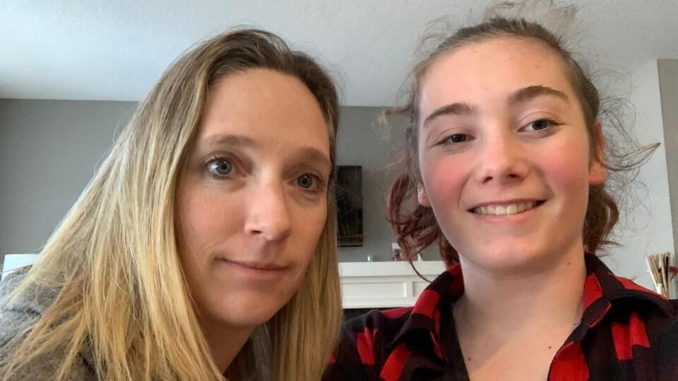 Deux femmes posent ensemble devant la caméra. L'une a des cheveux longs raides. L'autre plus jeune a une queue de cheval et des cheveux bouclés.