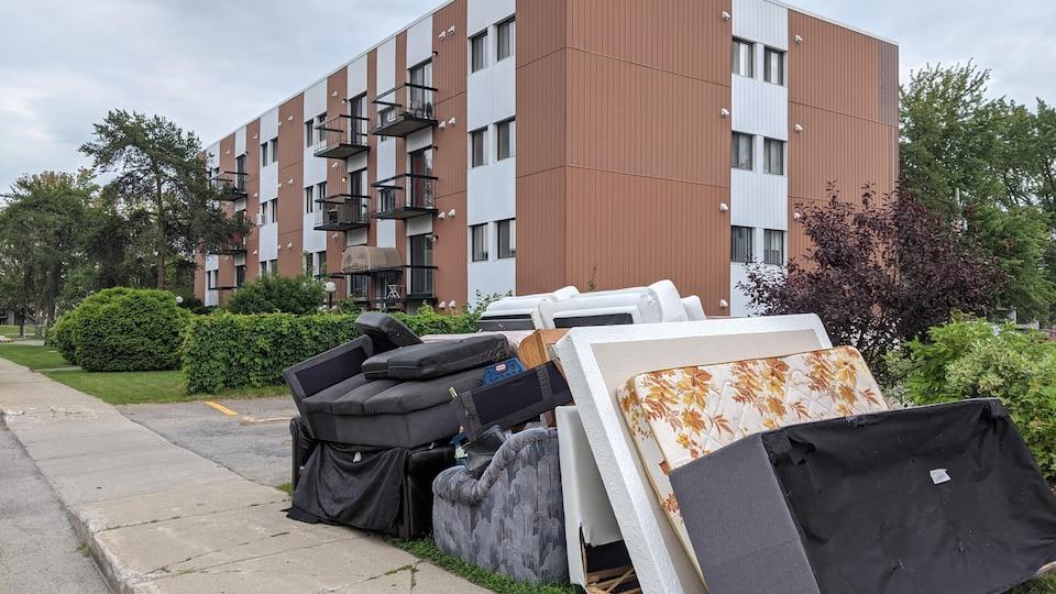 Meubles près du trottoir devant un immeuble à logements