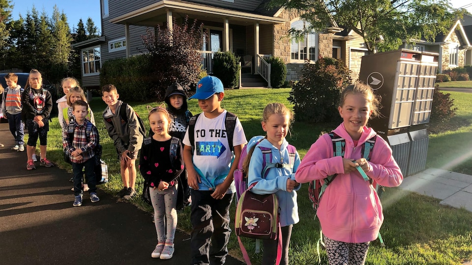 Des enfants attendent l'autobus.