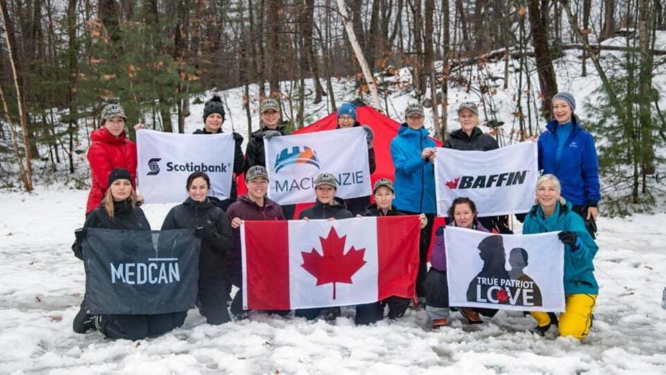 L'équipe tient des drapeaux. Elle s'est rencontrée pour s'entrainer avant l'expédition.
