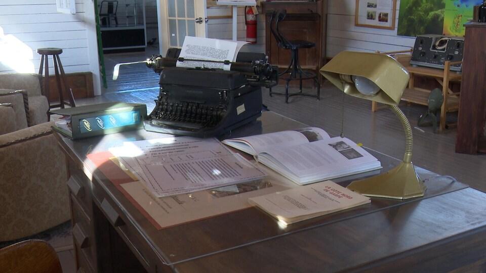 Une machine à écrire, des livres ouverts et une lampe ancienne déposés sur un bureau.
