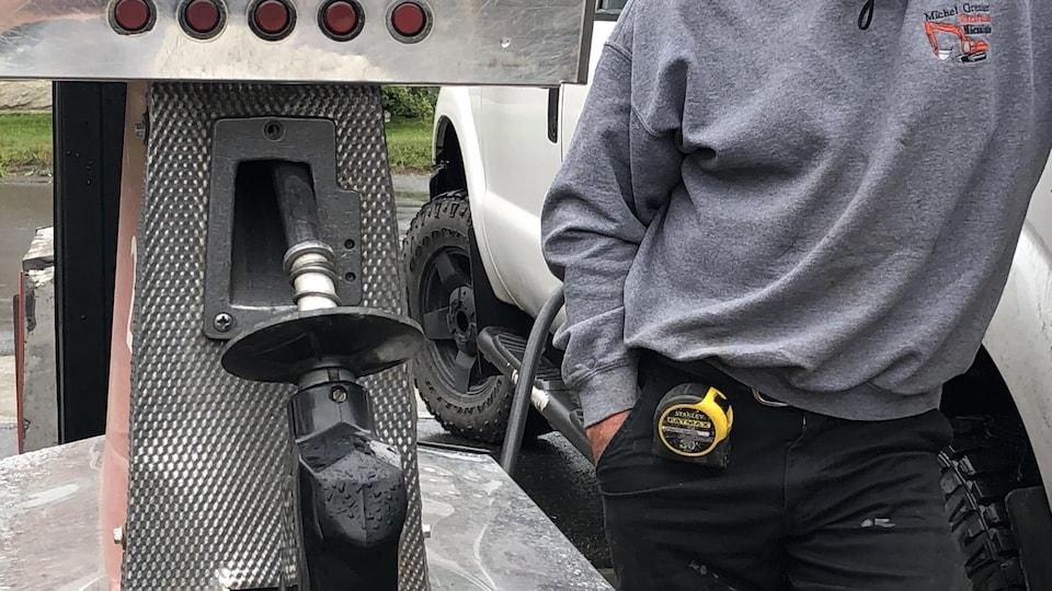 Un homme à côté d'une pompe à essence.