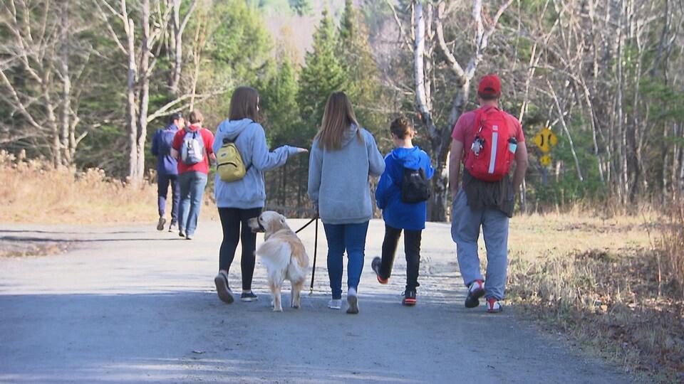 Une famille avec un chien se promène sur une piste de marche du mont Orford.