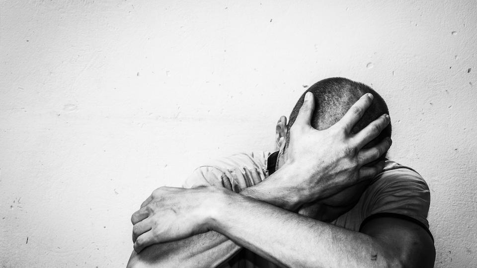 Un homme assis par terre, la tête appuyée dans sa main.