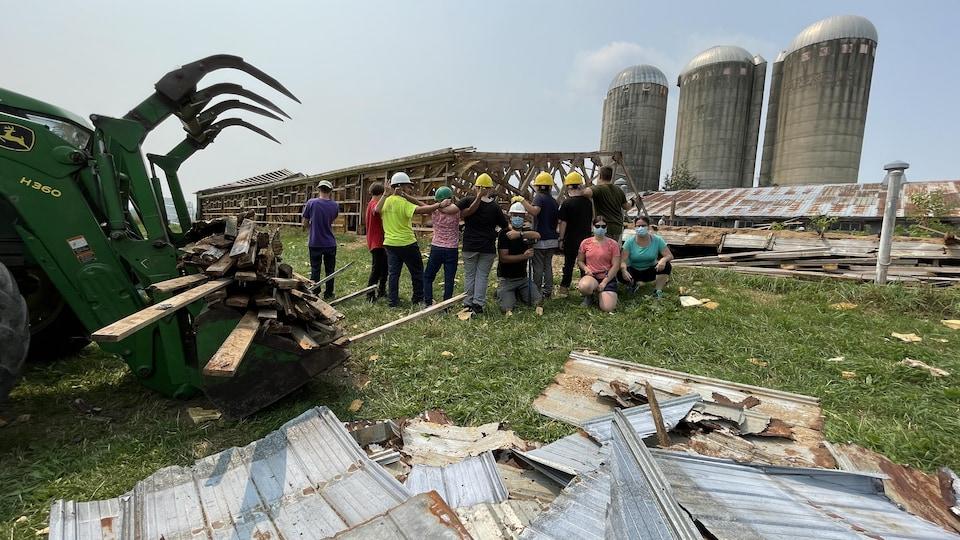 Des jeunes de dos devant une grange démolie