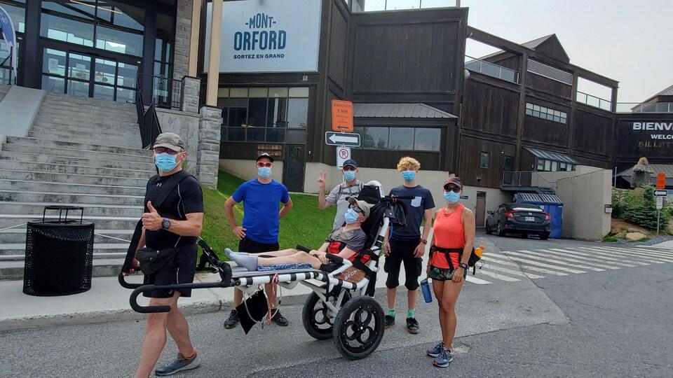 Fernand Courchesne et quatre autres bénévoles transportent un fauteuil roulant tout-terrain pour monter la montagne.
