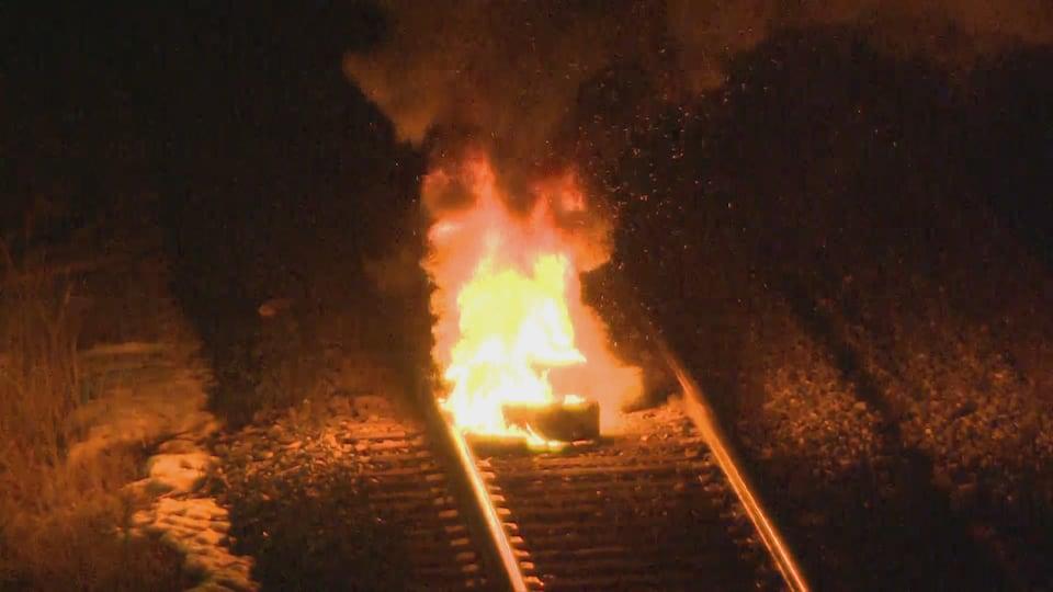Un pneu incendié sur une voie de chemin de fer.