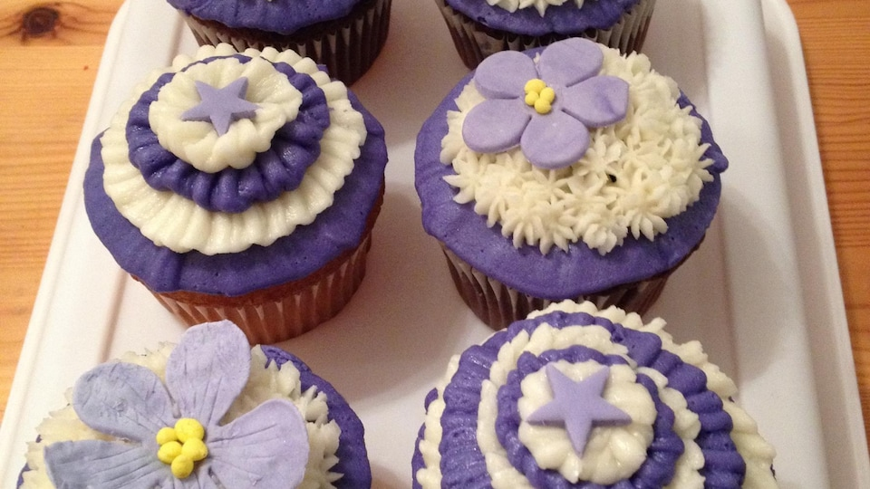 Des petits gâteaux décorés avec du glaçage blanc et violet. Ils ont des décorations en sucre, des fleurs et des étoiles.